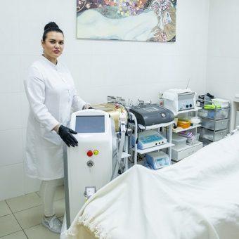 Косметолог салона красоты На Речной в Красногорске демонстрирует аппарат для лазерной эпиляции, готовый к процедуре.