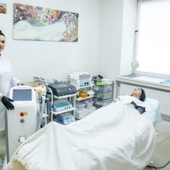 Косметолог салона красоты На Речной, демонстрирует аппараты для косметологических процедур, готовые к работе: здесь - аппарат для лазерной эпиляции.